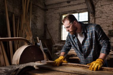 carpenter in protective gloves and googles using machine saw at sawmill