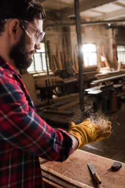 bearded craftsman in protective googles and gloves shaking off wooden chips from hands at sawmill