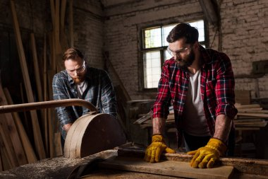 bearded carpenter in protective googles and gloves using machine saw and partner standing near at sawmill