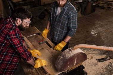 high angle view of two carpenters using machine saw at sawmill