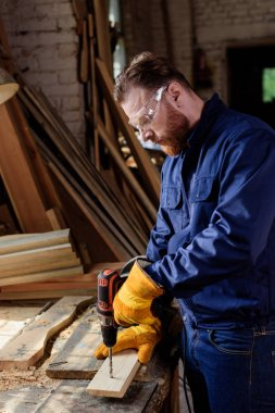 side view of bearded worker in protective gloves and googles using electric drill at sawmill
