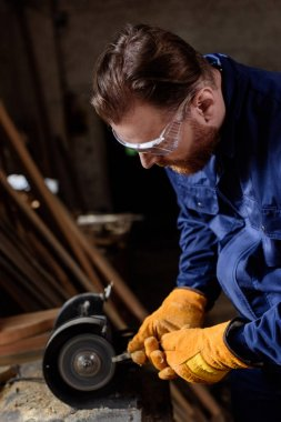 worker in protective googles and gloves using grinding machine at sawmill