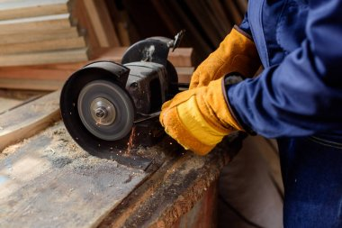 cropped shot of craftsman in protective gloves using grinding machine at sawmill