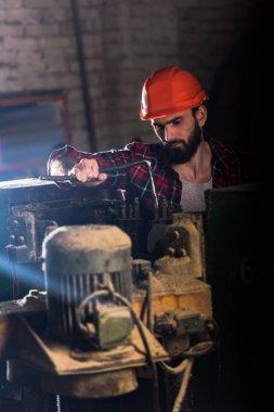 worker in protective helmet repairing machine tool at sawmill