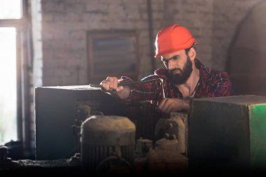 serious worker in protective helmet repairing machine tool at sawmill