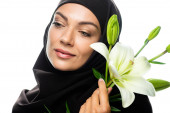 young Muslim woman in hijab holding lily and looking away isolated on white
