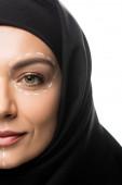 vista ritagliata di giovane donna musulmana in hijab con segni sul viso per la chirurgia plastica isolato su bianco