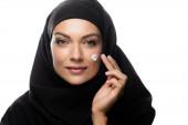 junge muslimische Frau im Hijab trägt kosmetische Creme auf Küken isoliert auf Weiß auf