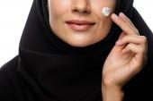 abgeschnittene Ansicht einer jungen muslimischen Frau im Hijab, die kosmetische Creme auf Küken aufträgt, isoliert auf Weiß