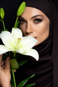 beautiful Muslim woman in hijab with smoky eyes holding lily isolated on black