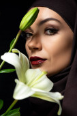 portrait of attractive Muslim woman in hijab with red lips holding lily isolated on black