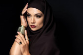 beautiful Muslim woman in hijab with makeup in golden rings and bracelet isolated on black