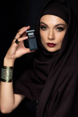 beautiful Muslim woman in hijab with makeup in golden jewelry holding perfume isolated on black