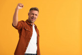 excited man with clenched fist celebrating isolated on orange