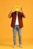 Kiev, Ucraina - 24 settembre 2019: uomo che copre il volto con emoticon felice sullarancio