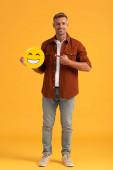 KYIV, UKRAINE - SEPTEMBER 24, 2019: cheerful man pointing with finger at happy emoji on orange