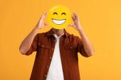 KYIV, UKRAINE - SEPTEMBER 24, 2019: man covering face with happy emoticon isolated on orange