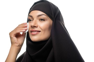 Smiling young Muslim woman in hijab wiping face with cotton pad isolated on white stock vector
