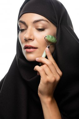 young Muslim woman in hijab using jade roller isolated on white