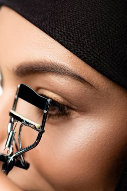 Close up view of young Muslim woman in hijab using eyelash curler stock vector