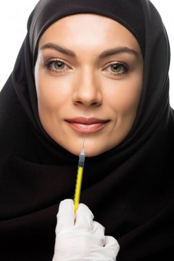 Young Muslim woman in hijab having beauty injection isolated on white, lip augmentation concept stock vector