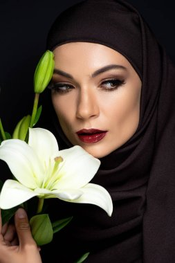 Beautiful Muslim woman in hijab with smoky eyes and red lips holding lily isolated on black stock vector