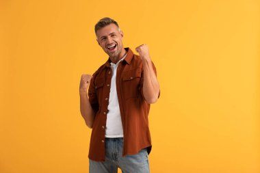 excited man with clenched fists isolated on orange