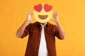 Kiev, Ucraina - 24 settembre 2019: uomo che copre il viso con gli occhi del cuore emoticon cartone animato isolato su arancione