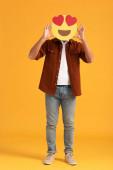 Kiev, Ucraina - 24 settembre 2019: uomo che copre il viso con gli occhi del cuore emoticon cartone animato su arancione