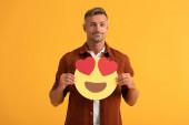 Kiev, Ucraina - 24 settembre 2019: bel uomo che tiene gli occhi del cuore emoticon cartone animato isolato su arancione