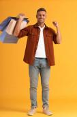 veselý muž drží barevné nákupní tašky na oranžové