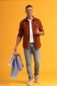 veselý muž drží barevné nákupní tašky a ukazující palec nahoru na oranžové