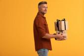 veselý muž drží dárky izolované na oranžové