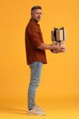 meglepett férfi gazdaság ajándékok, miközben áll a narancs