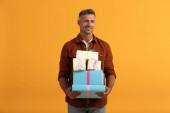 jóképű férfi mosolyog, miközben kezében ajándékdobozok elszigetelt narancs