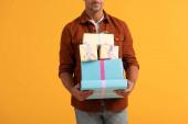 oříznutý pohled na muže usmívajícího se při držení dárkových krabic izolovaných na oranžové