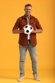 emotional man holding football and standing on orange