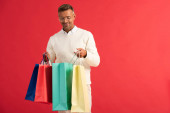 veselý muž v brýlích drží barevné nákupní tašky izolované na červené