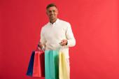 boldog férfi szemüvegben kezében színes bevásárló táskák elszigetelt piros