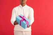 oříznutý pohled na usmívajícího se muže držícího dárkovou krabici izolovanou na červené