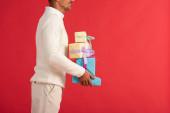 kivágott kilátás mosolygós ember gazdaság ajándék dobozok elszigetelt piros