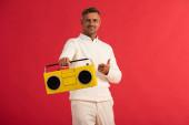 šťastný muž drží retro boombox a ukazuje prstem izolované na červené