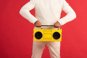 Fotografie cropped view of man holding retro boombox isolated on red