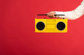 cropped view of man holding yellow boombox isolated on red