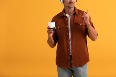 cropped view of happy man listening music and pointing with finger while holding coffee to go isolated on orange