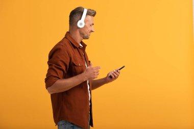 happy man listening music and holding smartphone isolated on orange