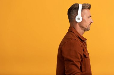 side view of handsome man in wireless headphones listening music isolated on orange