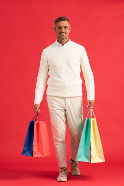 Cheerful man in glasses holding colorful shopping bags on red stock vector