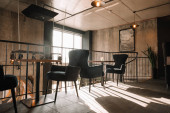 balkon se stoly a židlemi v moderní podkrovní kavárně na slunci