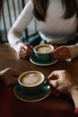 cropped view of couple drinking cappuccino on balcony in coffee shop